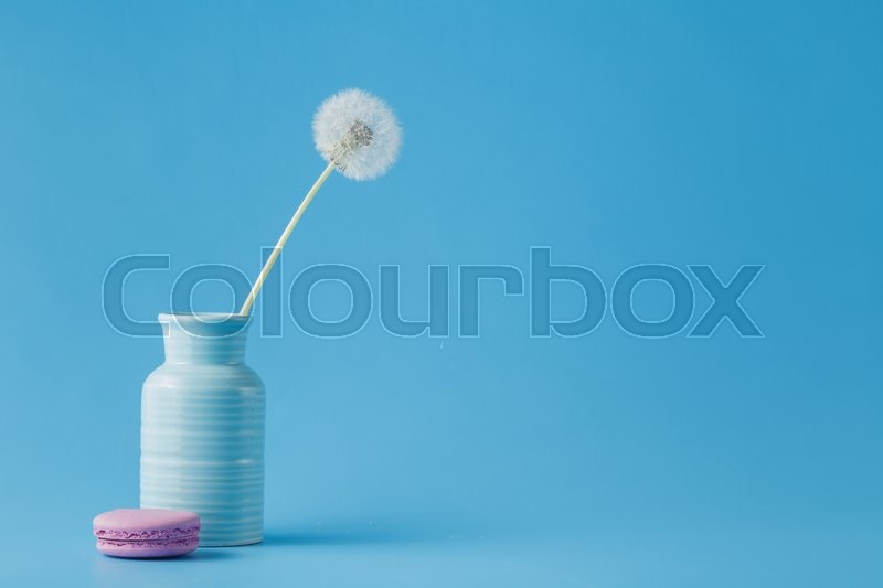Stock image of 'dandelions in vase and macaroon. Minimal design with copy space'