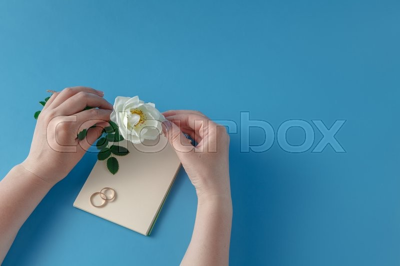 Stock image of 'Female writing wedding invitation and see on white rose'