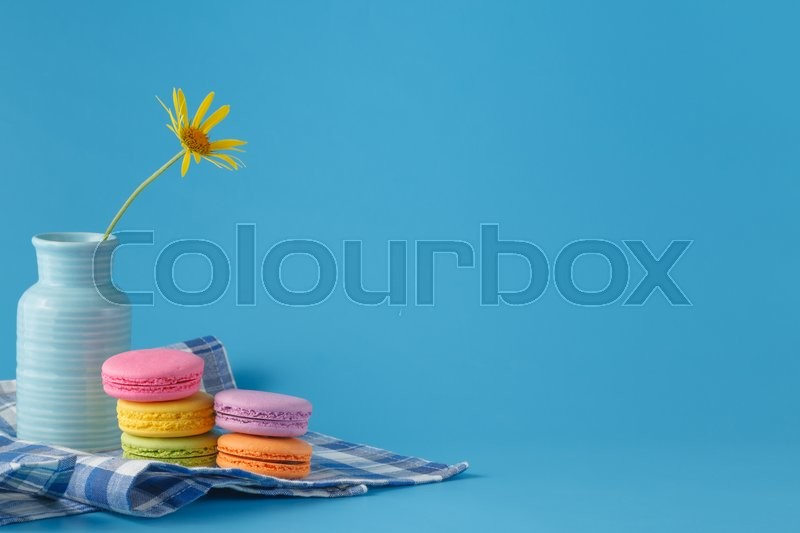 Stock image of 'Pile of macaroons and yellow flower with copy space on light background'