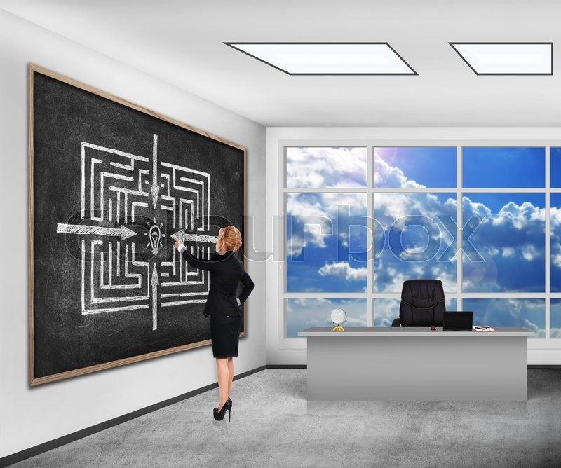 Stock image of 'businesswoman in classroom pointing on blackboard with drawing maze to success'