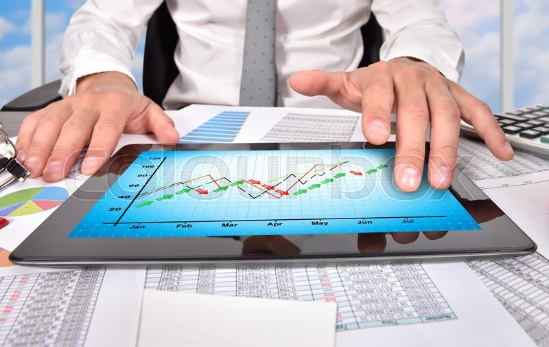 Stock image of 'hands using digital tablet with stock chart on screen'