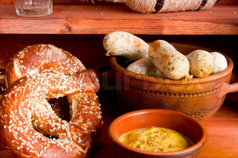 Stock image of 'German pretzels and sausages on wooden background'