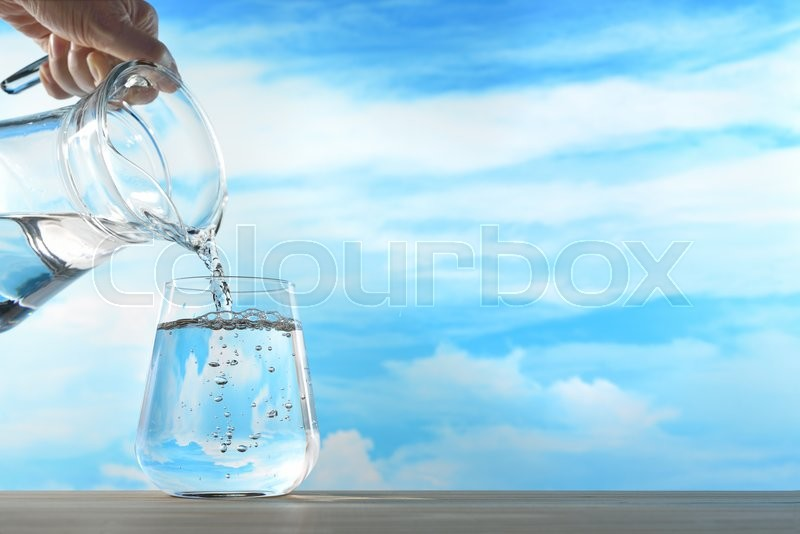 Stock image of 'Fresh and clean drinking water being poured from jug into glass on sky background'