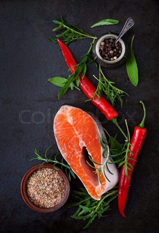 Stock image of 'Raw steak salmon and vegetables for cooking on a black background. Dietary menu. Proper nutrition. Top view'
