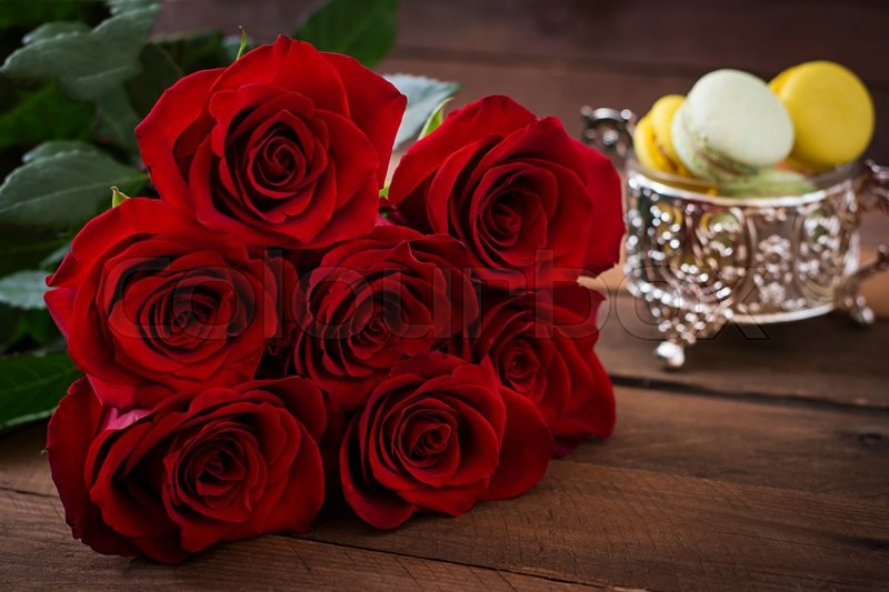 Stock image of 'Bouquet of red roses on a dark wooden background.'