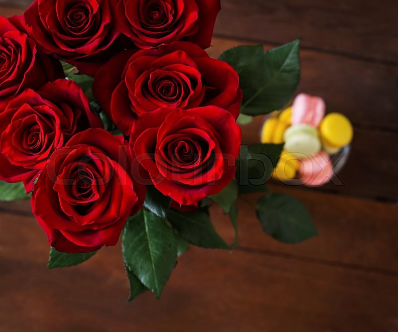Stock image of 'Bouquet of red roses on a dark wooden background. Top view'