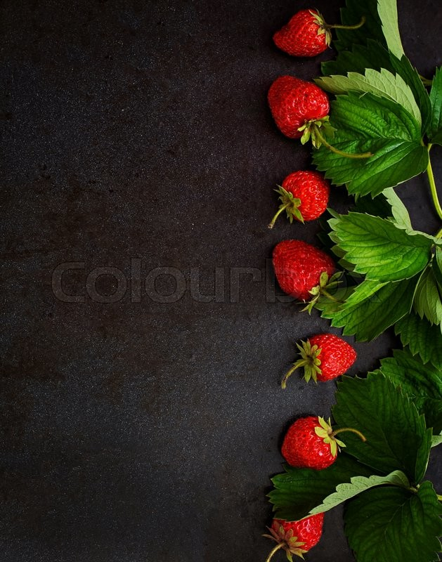 Stock image of 'Ripe strawberries and leaves on a black background. Top view'
