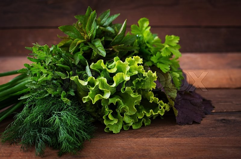 Stock image of 'Variety fresh organic herbs (lettuce, arugula, dill, mint, red lettuce and onion) on wooden background in rustic style.'