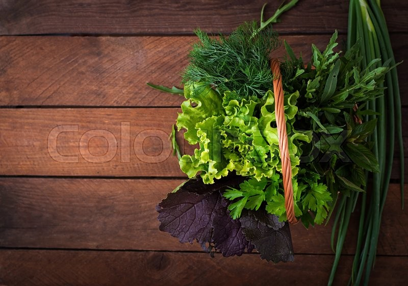 Stock image of 'Variety fresh organic herbs (lettuce, arugula, dill, mint, red lettuce and onion) on wooden background in rustic style. Top view'