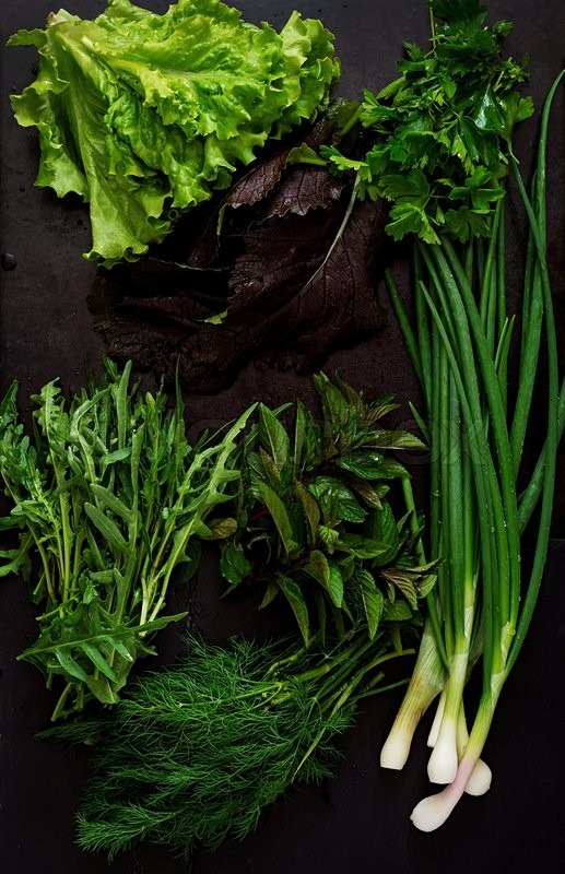 Stock image of 'Variety fresh organic herbs (lettuce, arugula, dill, mint, red lettuce and onion) on black background in rustic style. Top view'