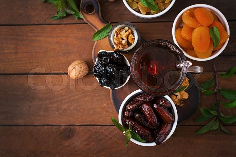 Stock image of 'Mix dried fruits (date palm fruits, prunes, dried apricots, raisins) and nuts, and traditional Arabic tea. Ramadan (Ramazan) food. Top view'