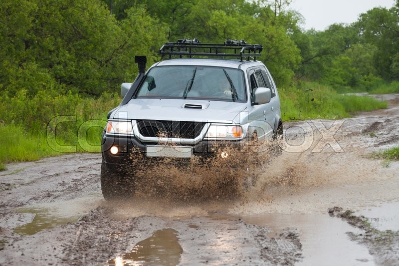 Stock image of 'Mitsubishi Pajero moving by water in the rain making lots of splashes'