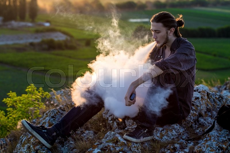 Stock image of 'Handsome young man sitting on a rocks and smoking electronic cigarette at outdoors.'