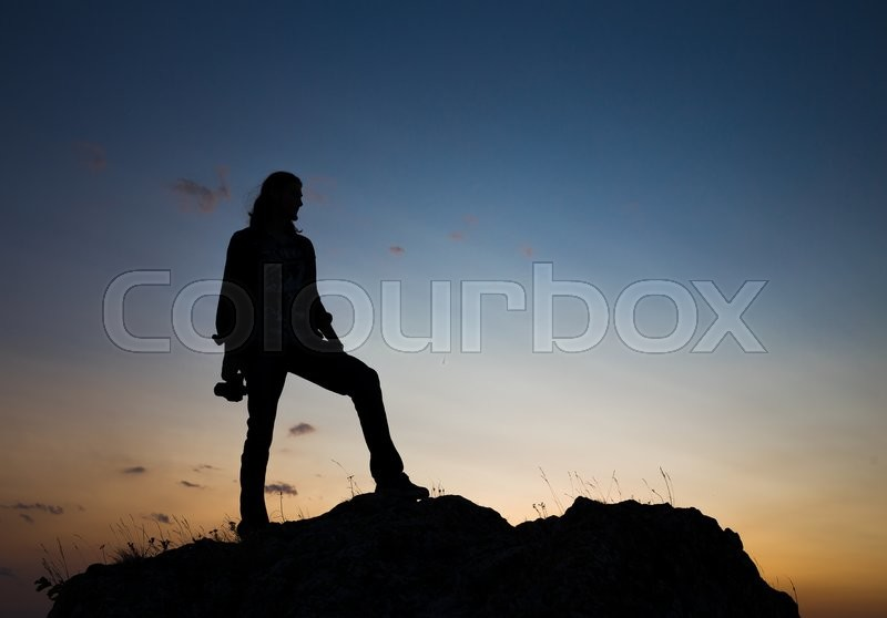 Stock image of 'Silhouette of young longhair male model with dslr camera at blue and yellow sunset.'