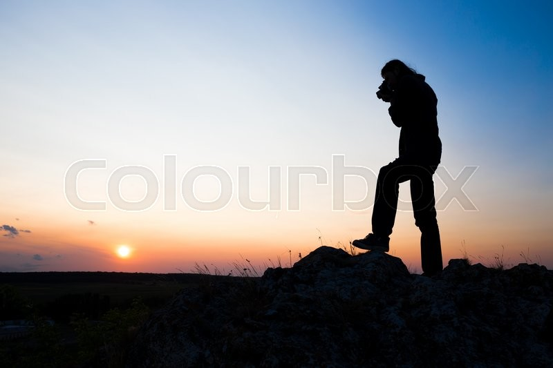 Stock image of 'Silhouette of young longhair male model making photo shot with dslr camera at blue and yellow sunset.'