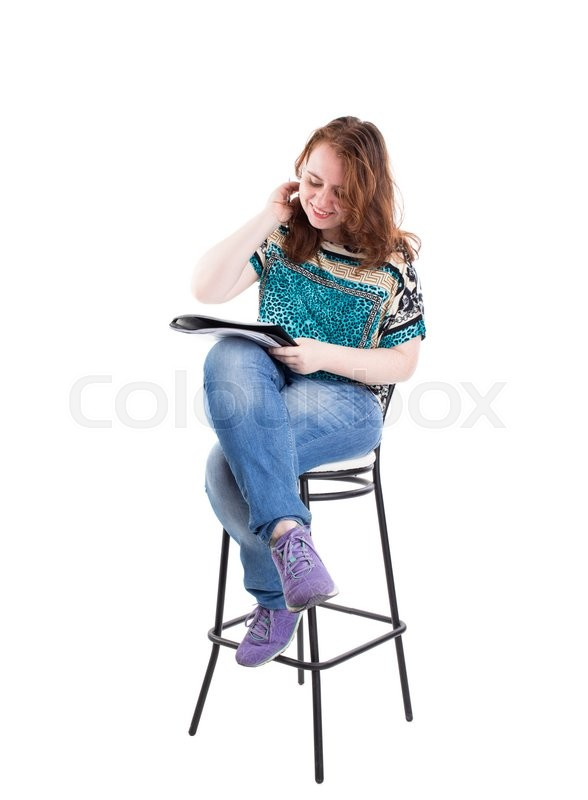 Stock image of 'Beautiful smiling redhead plus size wreckled model with folder and ballpoint pen sitting on the bar chair. Isolated on a white background.'