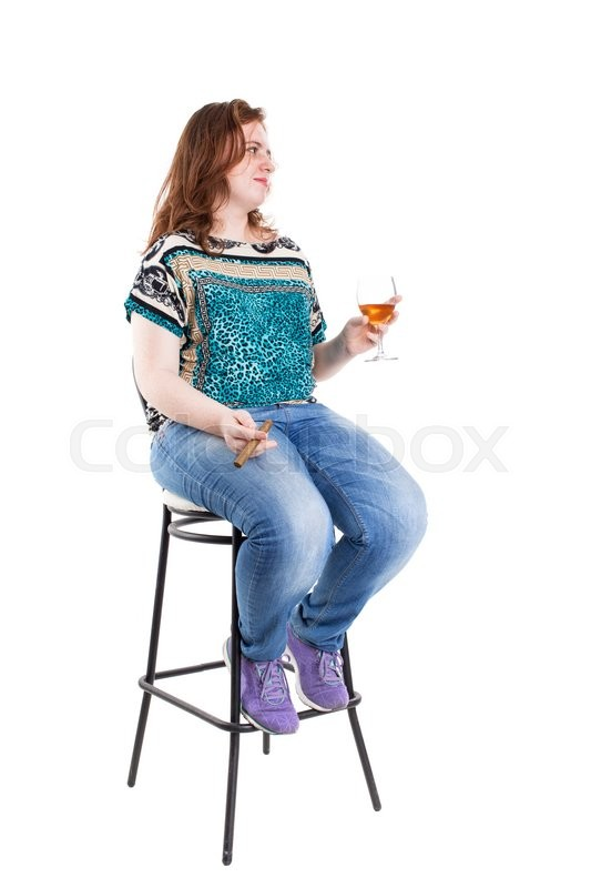 Stock image of 'Smiling redhead plus size wreckled model sitting on the bar chair with glass of whiskey and cigar. Studio shot. Isolated on a white background.'