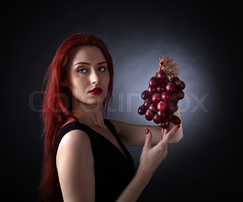 Stock image of 'Beautiful redheaded woman in a black dress with grape'