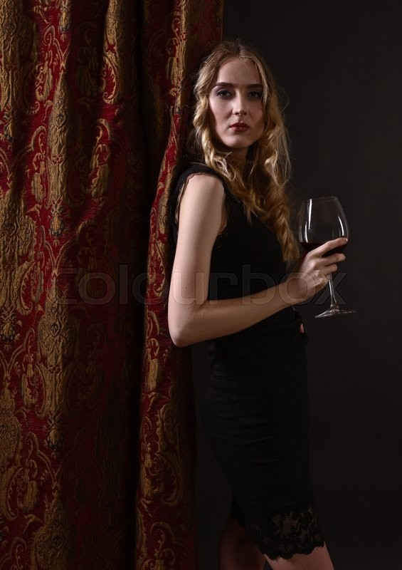 Stock image of 'young beautiful woman with glass of red wine'