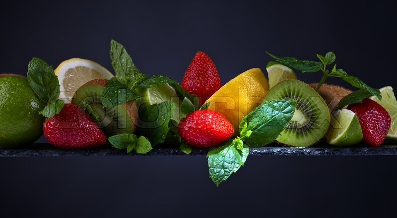Stock image of 'The ripe juicy fruits and peppermint leaves on a dark background'