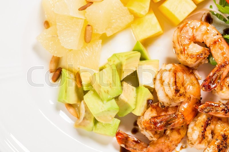 Stock image of 'Jumbo shrimp salad with avocado mango topped with pine nuts and parmesan cheese. Macro. Photo can be used as a whole background.'