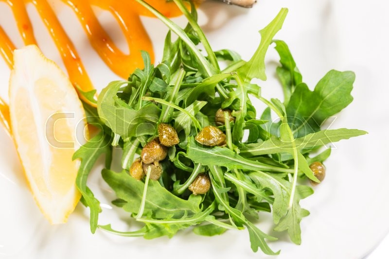 Stock image of 'Arugula with capers on apricot mousse as a garnish for baked salmon fillet. Macro. Photo can be used as a whole background.'