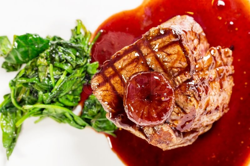 Stock image of 'Delicious grilled fillet mignon steak with chard covered with red wine sauce. Macro. Selective focus. Photo can be used as a whole background.'