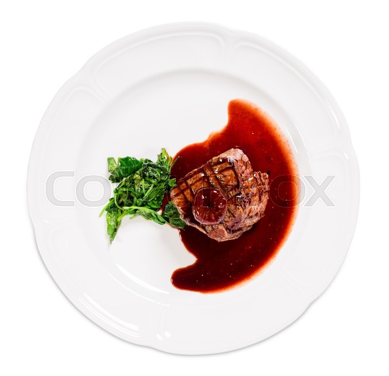 Stock image of 'Delicious grilled fillet mignon steak with chard covered with red wine sauce. Isolated on a white background.'