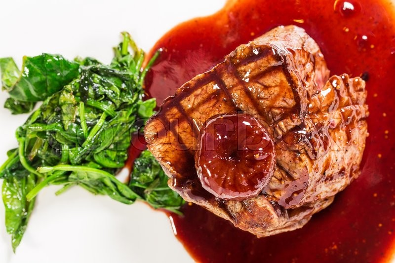 Stock image of 'Delicious grilled fillet mignon steak with chard covered with red wine sauce. Macro. Selective focus on the top of steak. Photo can be used as a whole background.'