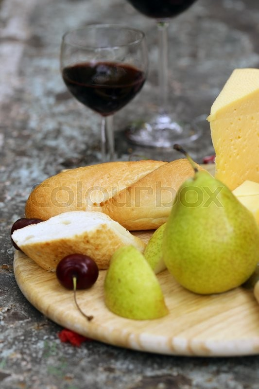 Stock image of 'Cheeseboard with pears and wine on a table in the garden'