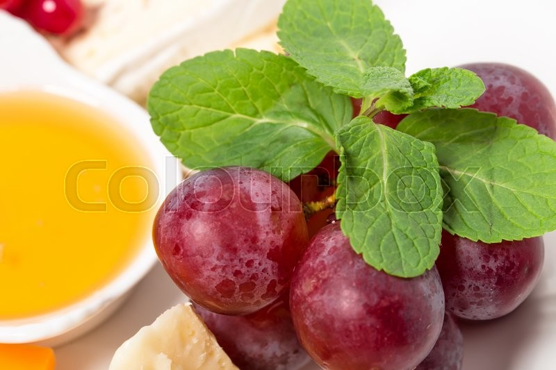 Stock image of 'Delicious cheese platter with red grapes and honey. Macro. Photo can be used as a whole background.'