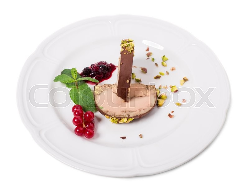 Stock image of 'Delicious foie gras covered with dark chocolate and pistacchio nuts with red berry jam and mint. Isolated on a white background.'