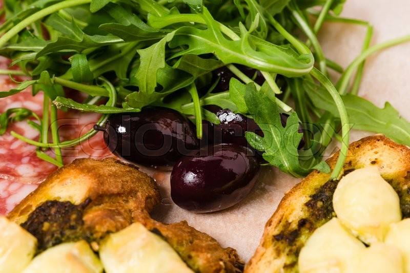 Stock image of 'Traditional tuscan antipasto platter with kalamata olives and fresh arugula. Macro. Photo can be used as a whole background.'