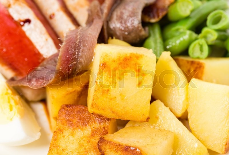 Stock image of 'Delicious nicoise salad with anchovies and baked potatoes. Macro. Photo can be used as a whole background.'