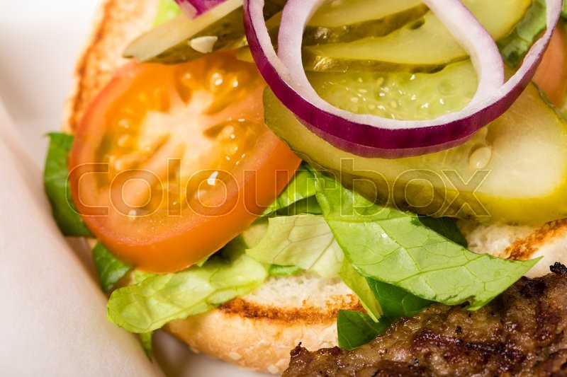 Stock image of 'Closeup of burger bun with sliced red onion and pickled tomatoes on lettuce leaves. Macro. Photo can be used as a whole background.'