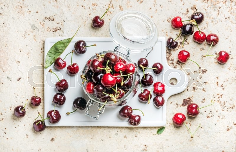 Stock image of 'Sweet cherry in glass jar on white ceramic board over concrete background, top view'