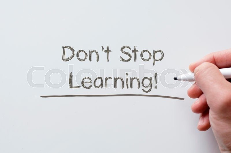 Stock image of 'Human hand writing don't stop learning on whiteboard'