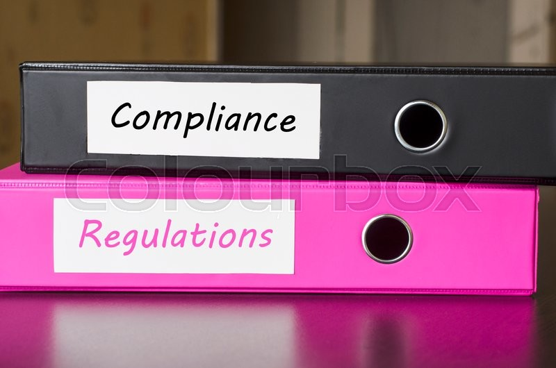 Stock image of 'Bright office folders over dark background and compliance regulations text concept'
