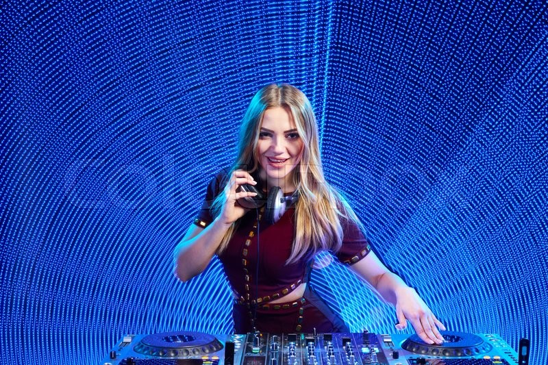 Stock image of 'Beautiful DJ girl on decks at the party over blue led background'