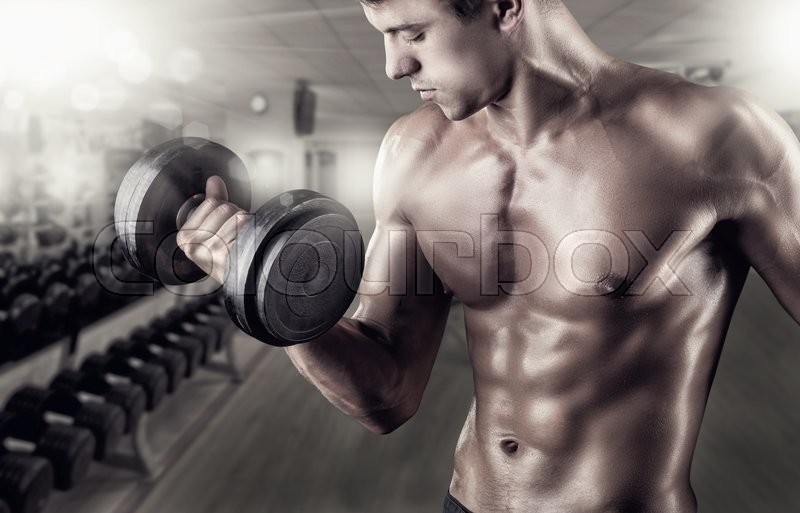 Stock image of 'Close Up of a muscular young man lifting weights in the gym'