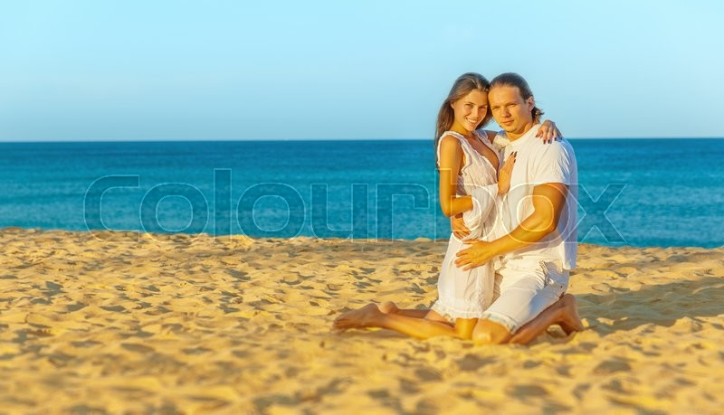 Stock image of 'Young beautiful couple sitting in each other's arms on the sand near the sea'