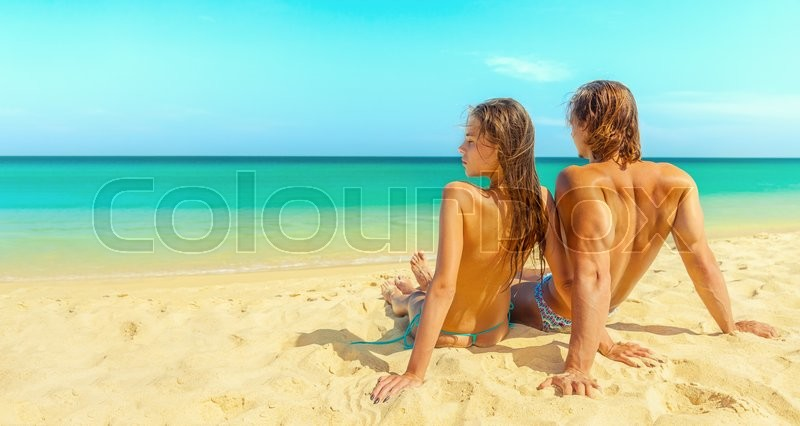 Stock image of 'Young couple sitting together on the sand and the sea, looking at the horizon dreaming'