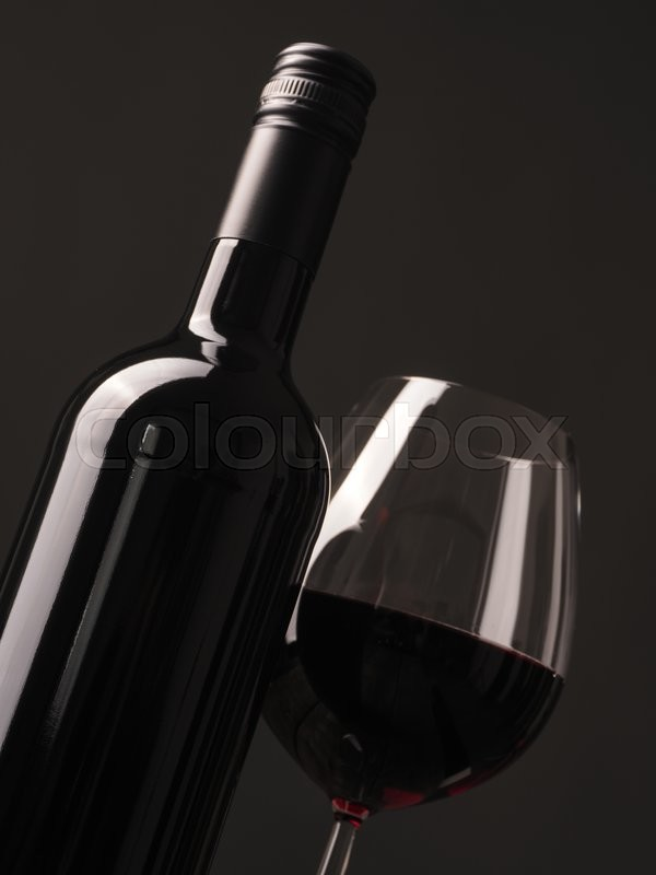 Stock image of 'Bottle and glass of red wine on a dark studio background'