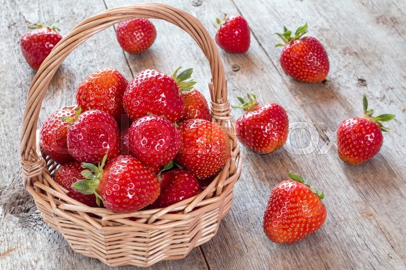Stock image of 'Fresh strawberries in a wicker basket on a white wooden background'