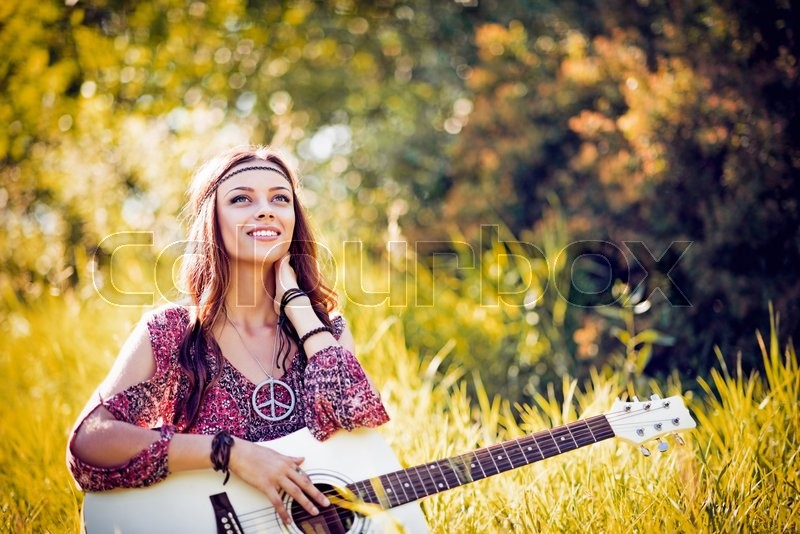Stock image of 'Portrait of a beautiful smiling hippie girl with guitar. Outdoor shot'