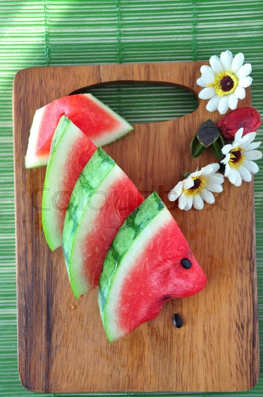 Stock image of 'Above of fresh watermelon pieces put on wooden board'