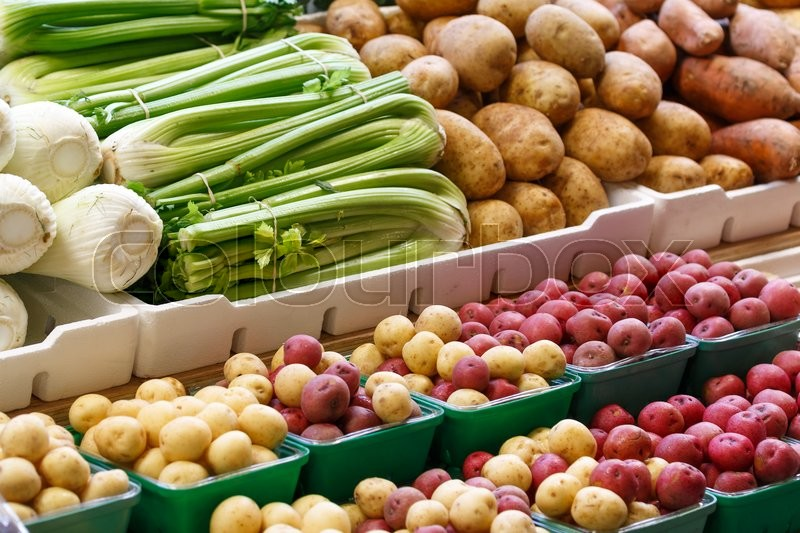 Stock image of 'Photo shows close-up view of various fruits and vegetables in the farmers market.'