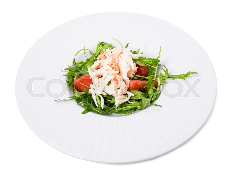 Stock image of 'Delicious snow crab salad with pomelo and arugula topped with pine nuts. Isolated on a white background.'