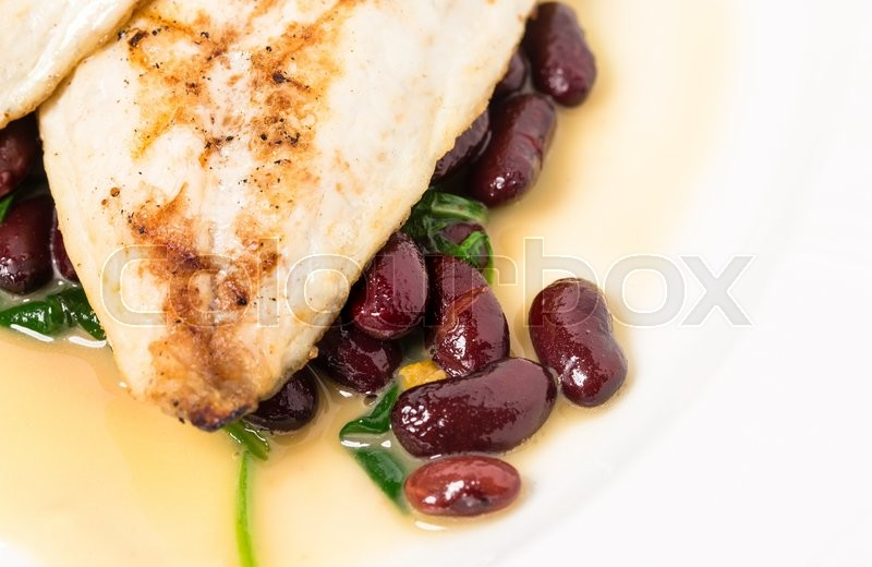 Stock image of 'Delicious baked dorado fillet with chard and beans. Macro. Phoro can be used as a whole background.'