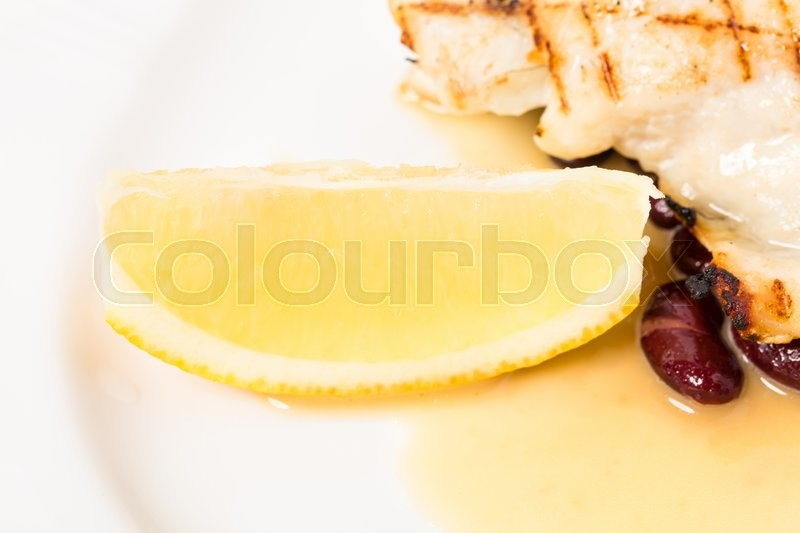 Stock image of 'Delicious baked dorado fillet with lemon and beans. Macro. Phoro can be used as a whole background.'